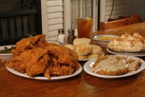 Fried chicken, chicken fried steak, coconut cream pie, and side dishes including: creamed corn, green beans, mashed potates and gravy, and buttermilk biscuits