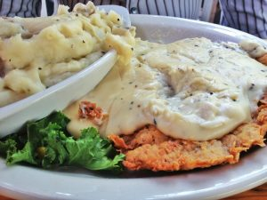 Chicken fried steak and mashed potatoes covered in white peppered gravy